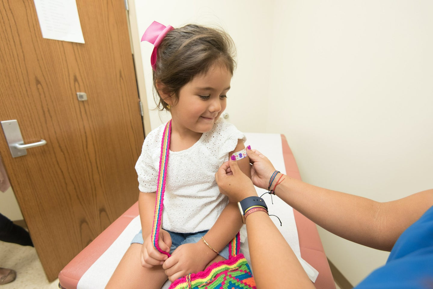 a girl getting a bandaid after receiving a vaccine.
