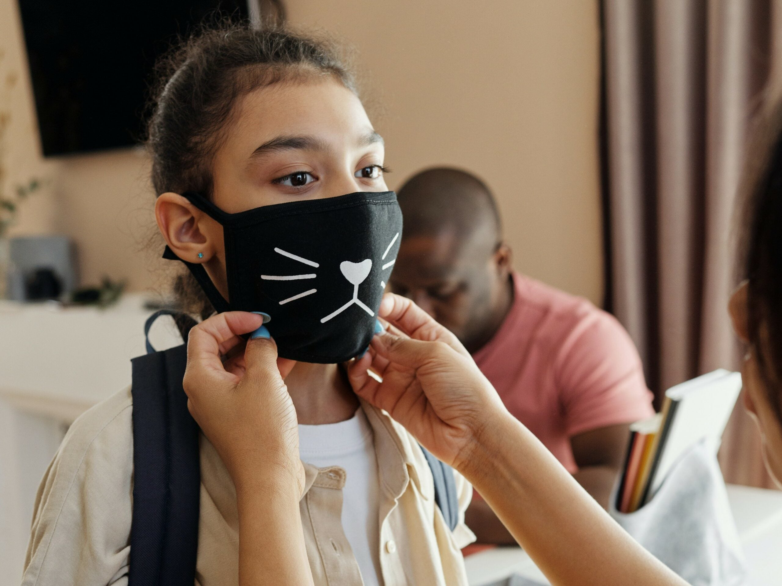 a mother putting a mask on her daughter