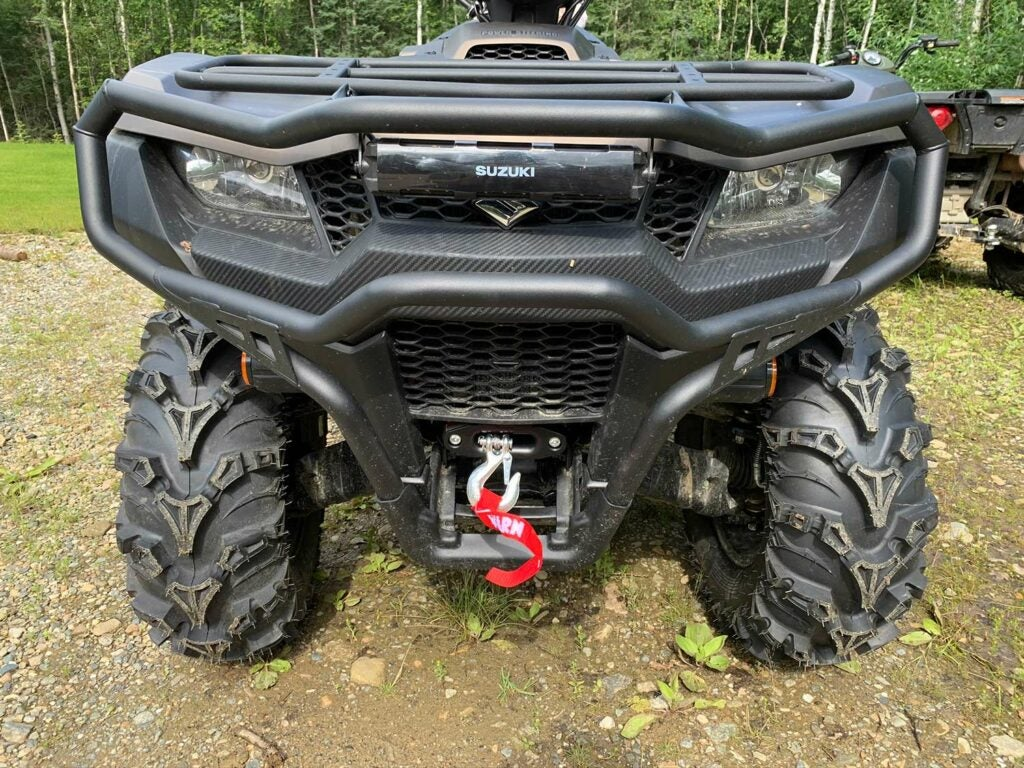 The front of a Suzuki four-wheeler ATV equipped with bumpers and a winch.