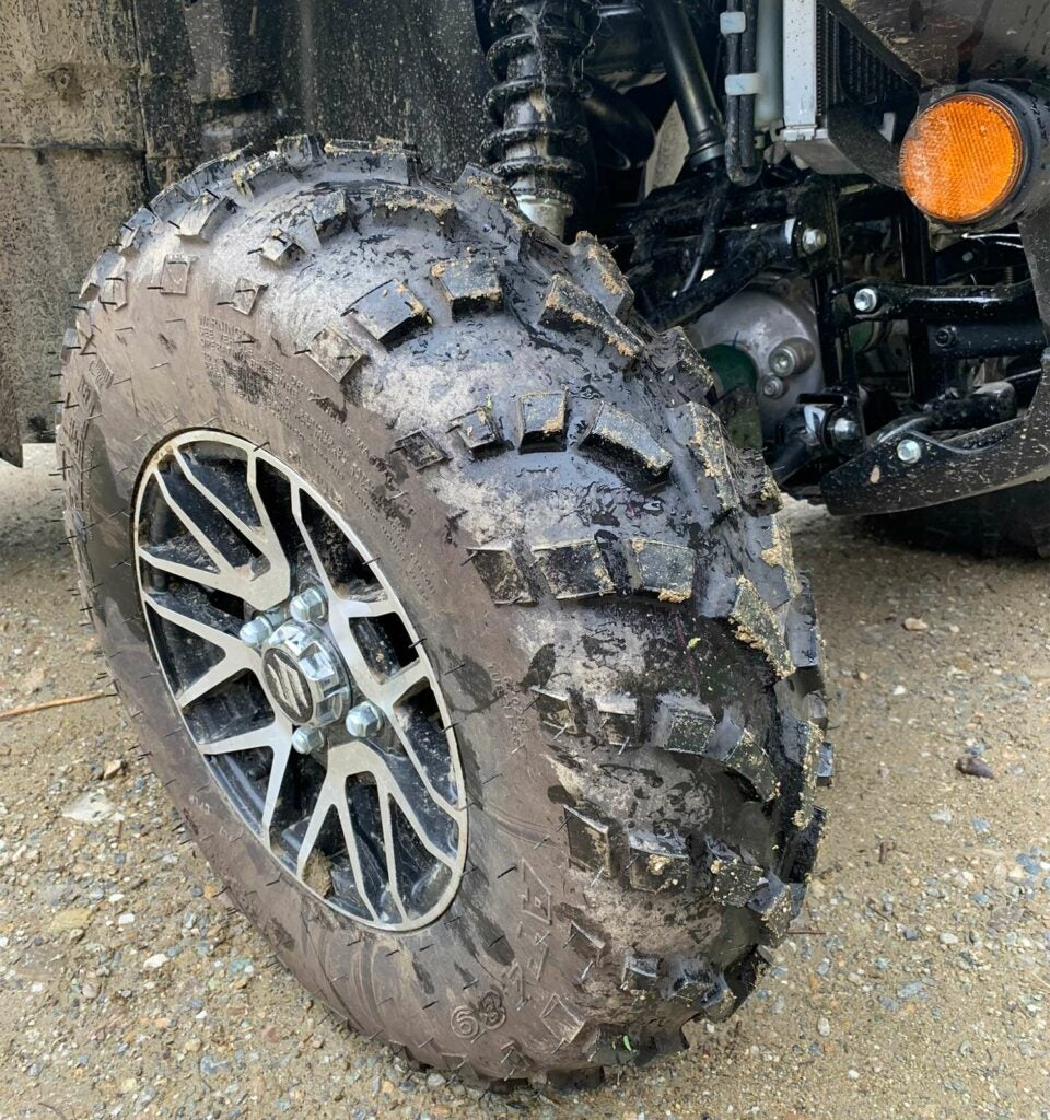 The wet and muddy tires of a Suzuki ATV four-wheeler.