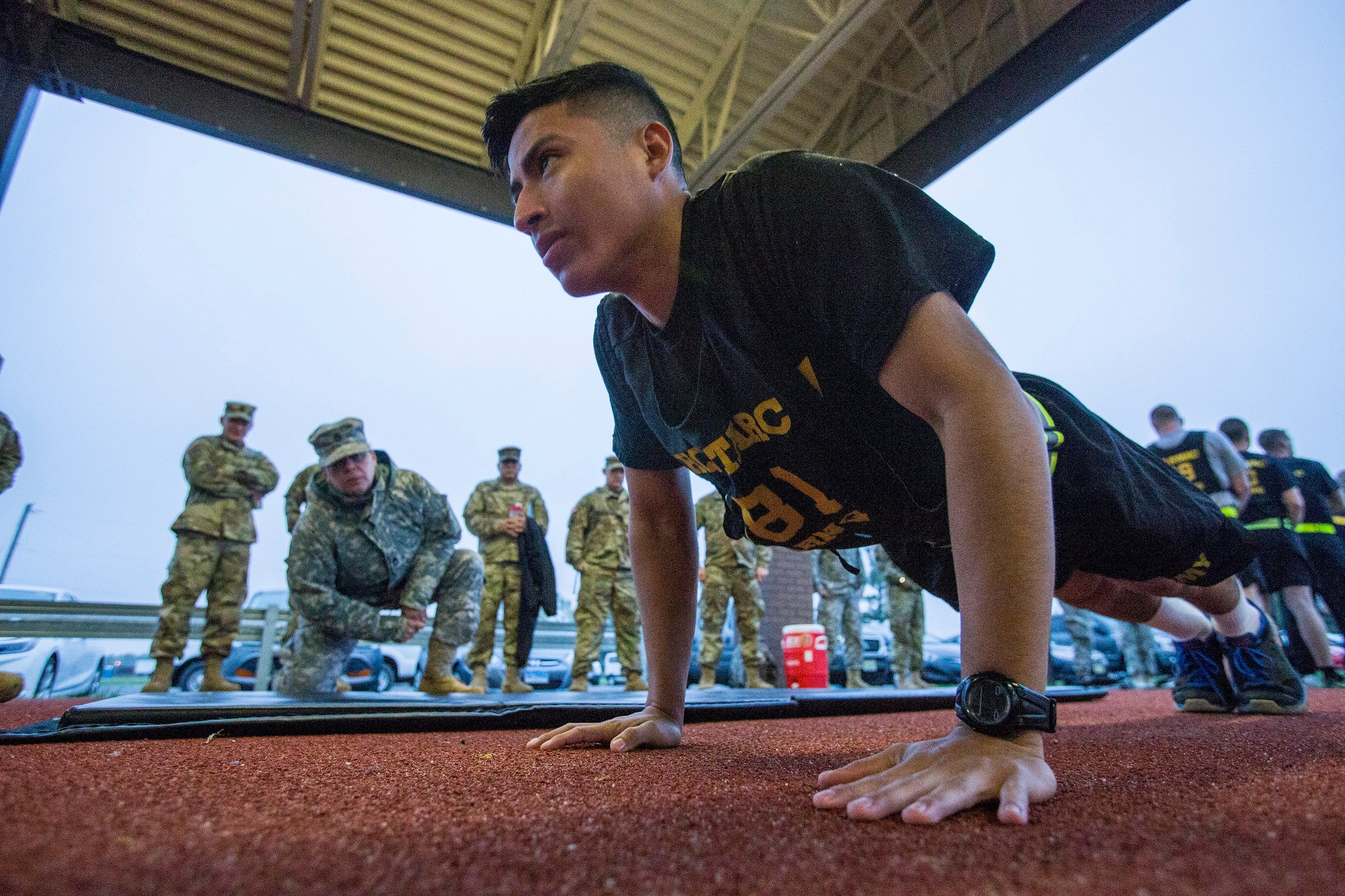A US Army National Guard soldier does a push-up in front of a drill sergeant