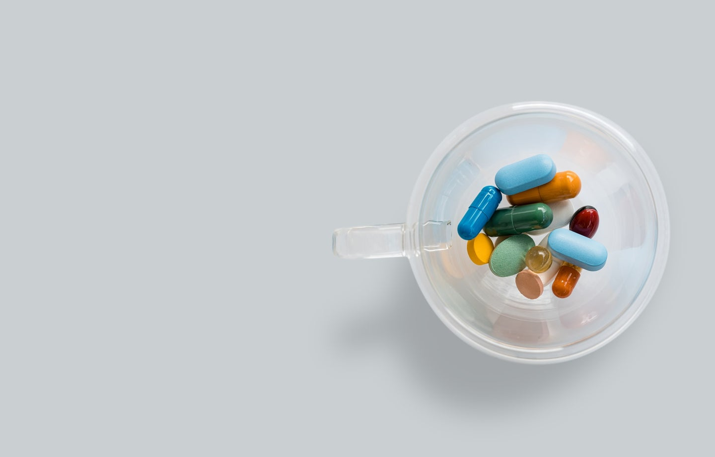 A cup full of multi-colored pills