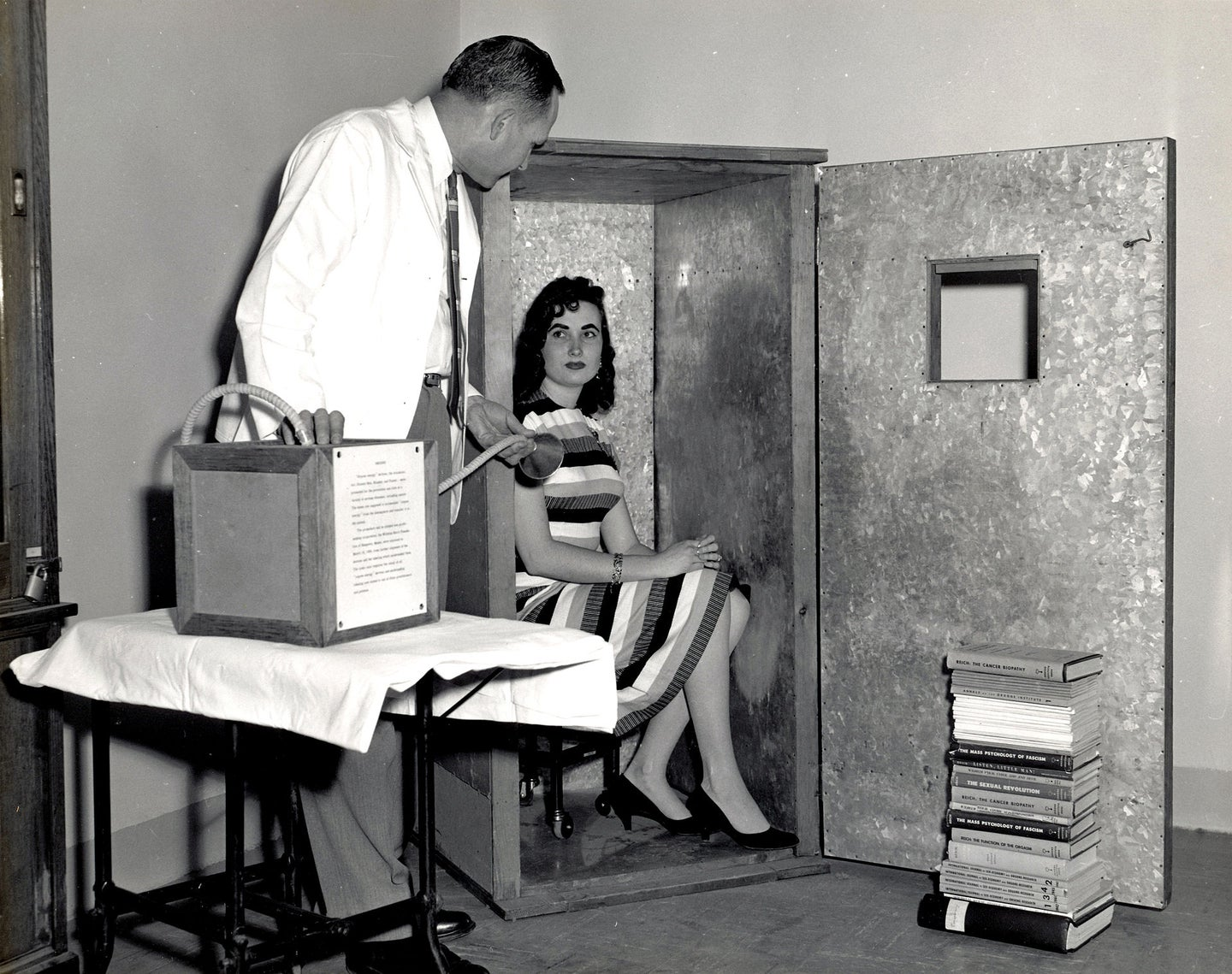 a woman sits in a metal box while a man speaks to her