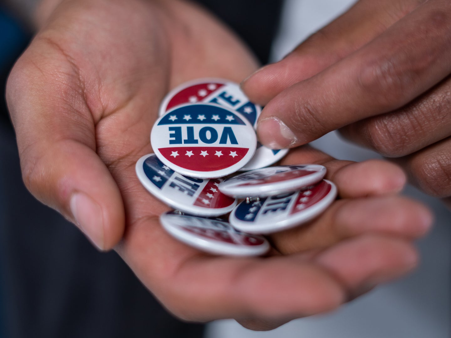 """a hand holding pins that say """"vote"""" on them"""