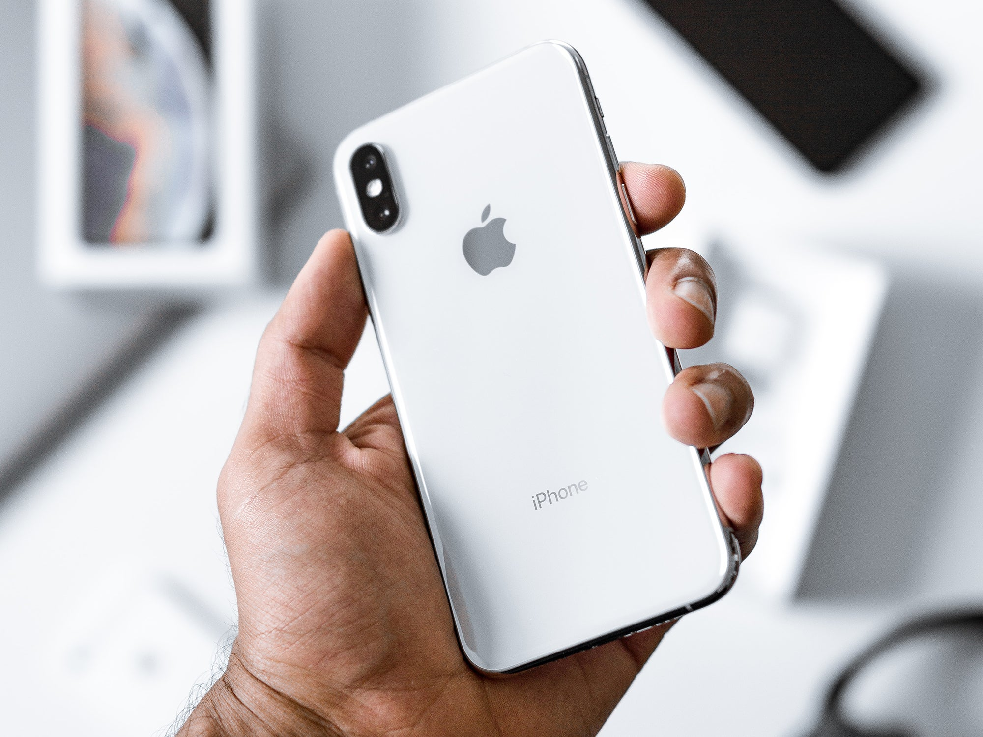 a person holding a white Apple iPhone in their hand