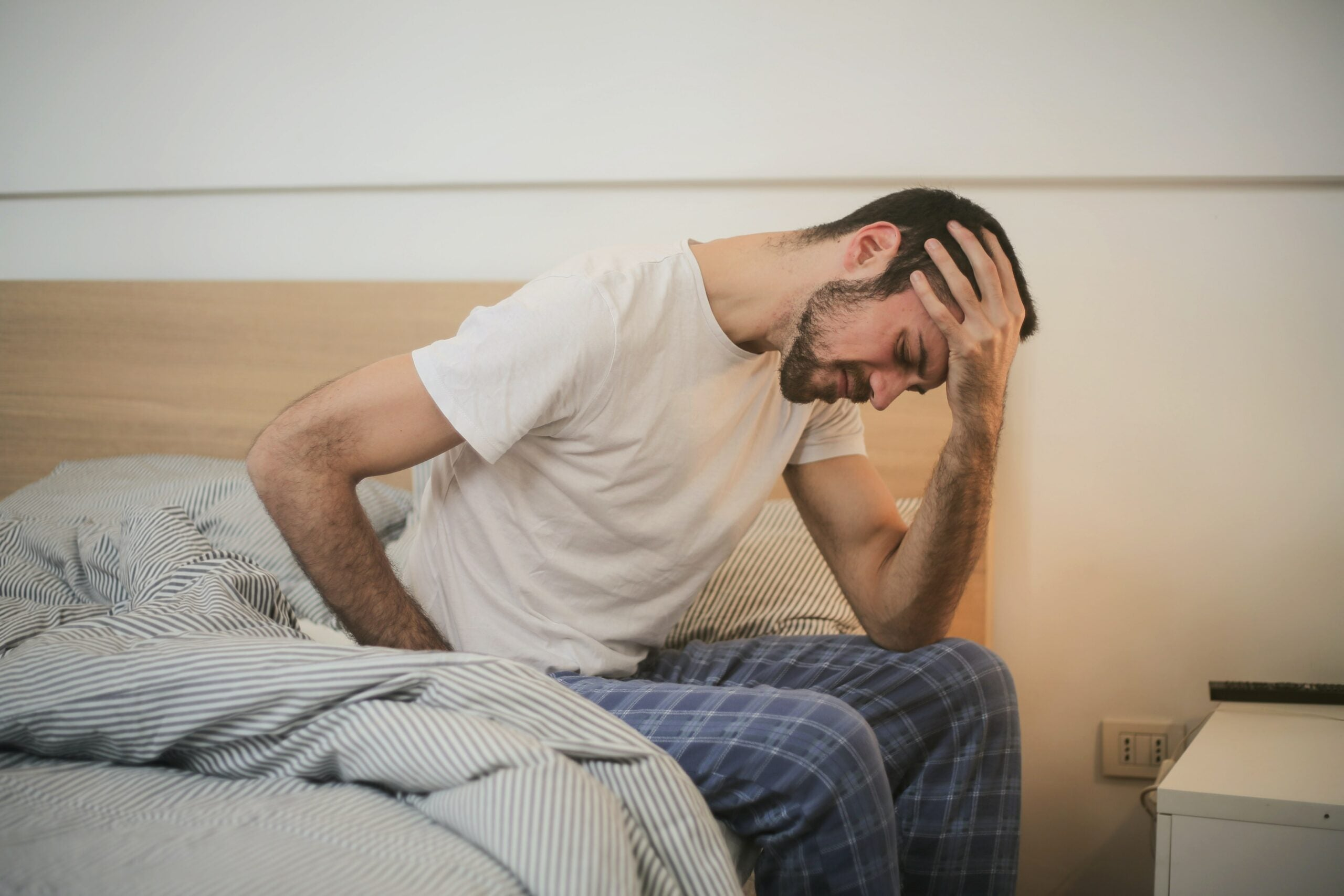 Man with headache on bed.
