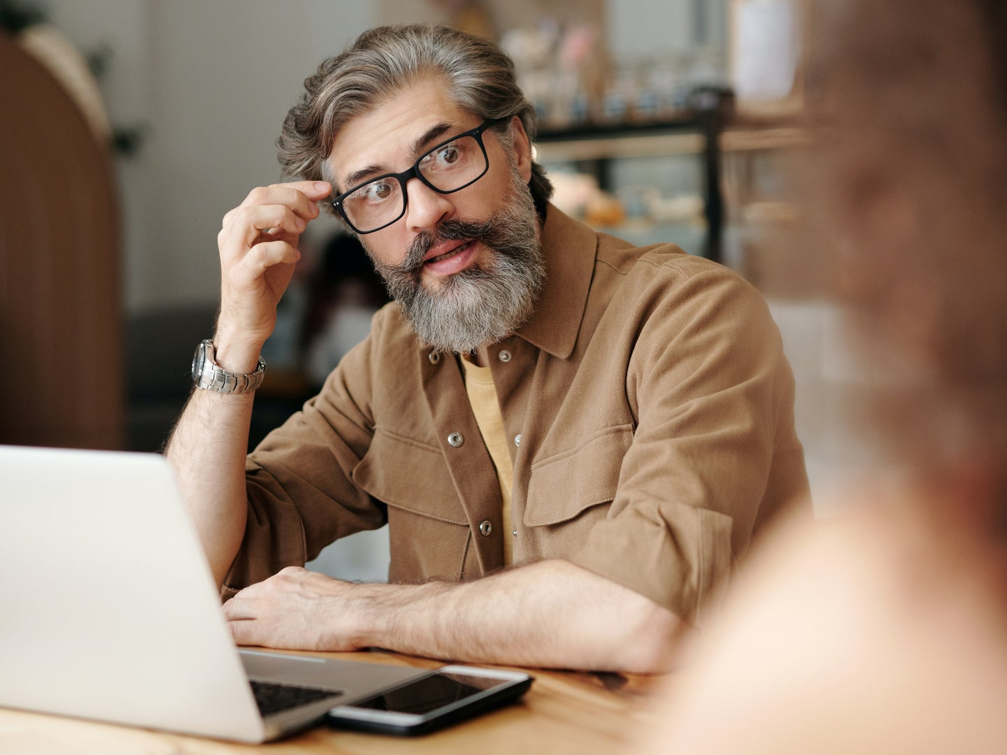 a bearded man with glasses looking stressed and confused while using a laptop computer