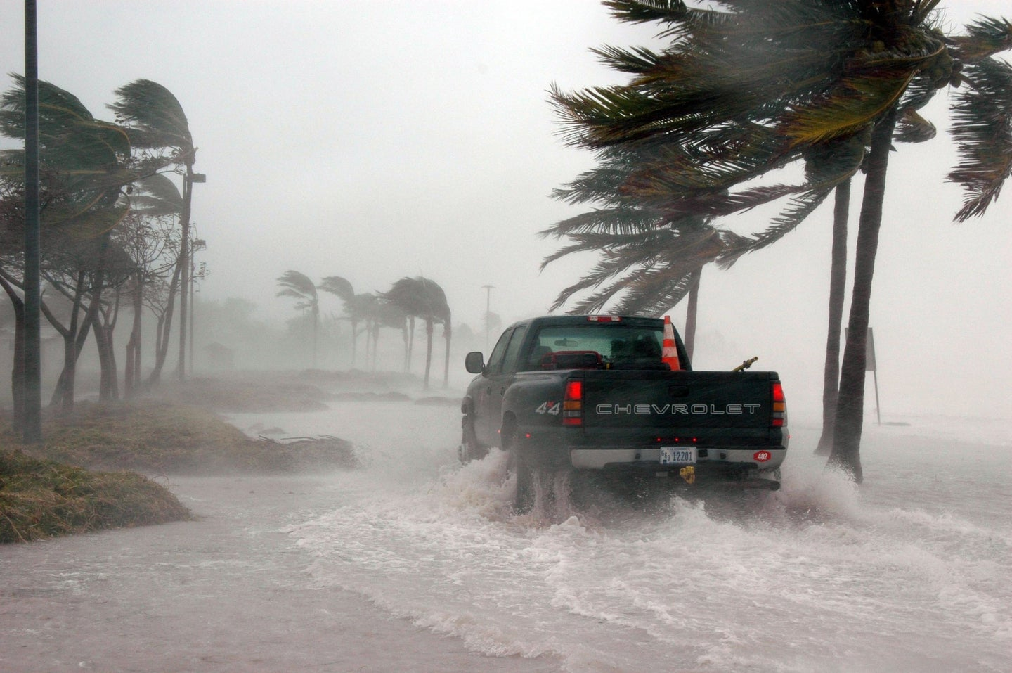 truck driving through water on beach as hurricane moves in