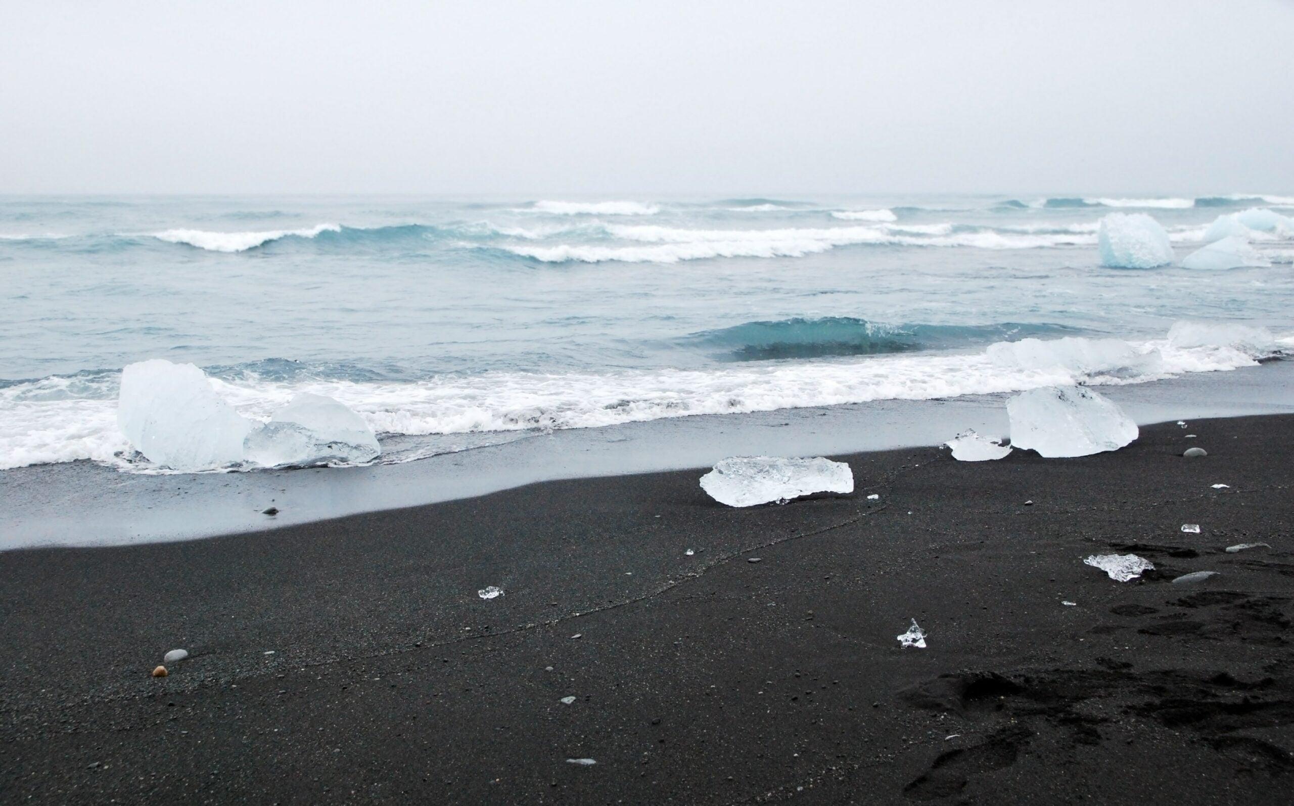 black sand beach with chunks of ice
