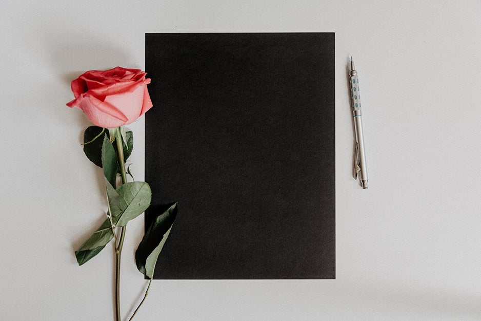 pencil, rose, and piece of black paper