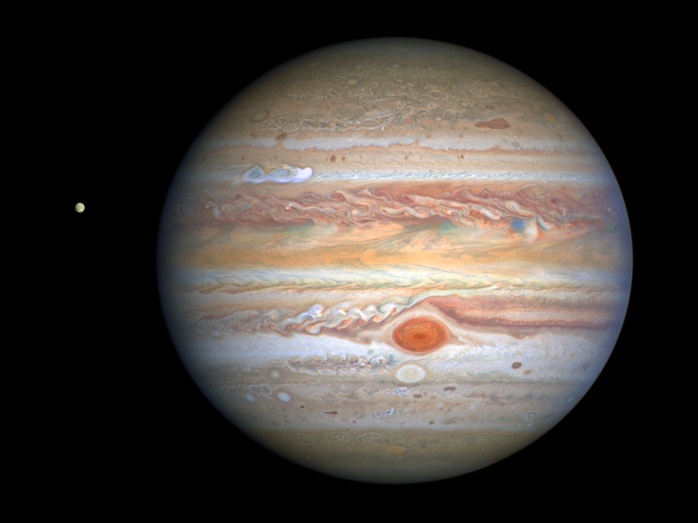 This latest image of Jupiter, taken by NASA's Hubble Space Telescope on Aug. 25, 2020, was captured when the planet was 406 million miles from Earth. A unique and exciting detail of Hubble's snapshot appears at mid-northern latitudes as a bright, white, stretched-out storm traveling around the planet at 350 mph. Hubble shows that the Great Red Spot, rolling counterclockwise in the planet's southern hemisphere, is plowing into the clouds ahead of it, forming a cascade of white and beige ribbons. Jupiter's icy moon Europa, thought to hold potential ingredients for life, is visible to the left of the gas giant.