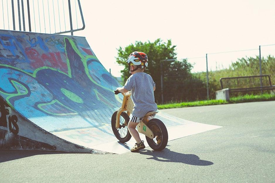 kid riding a bike up a skating ramp