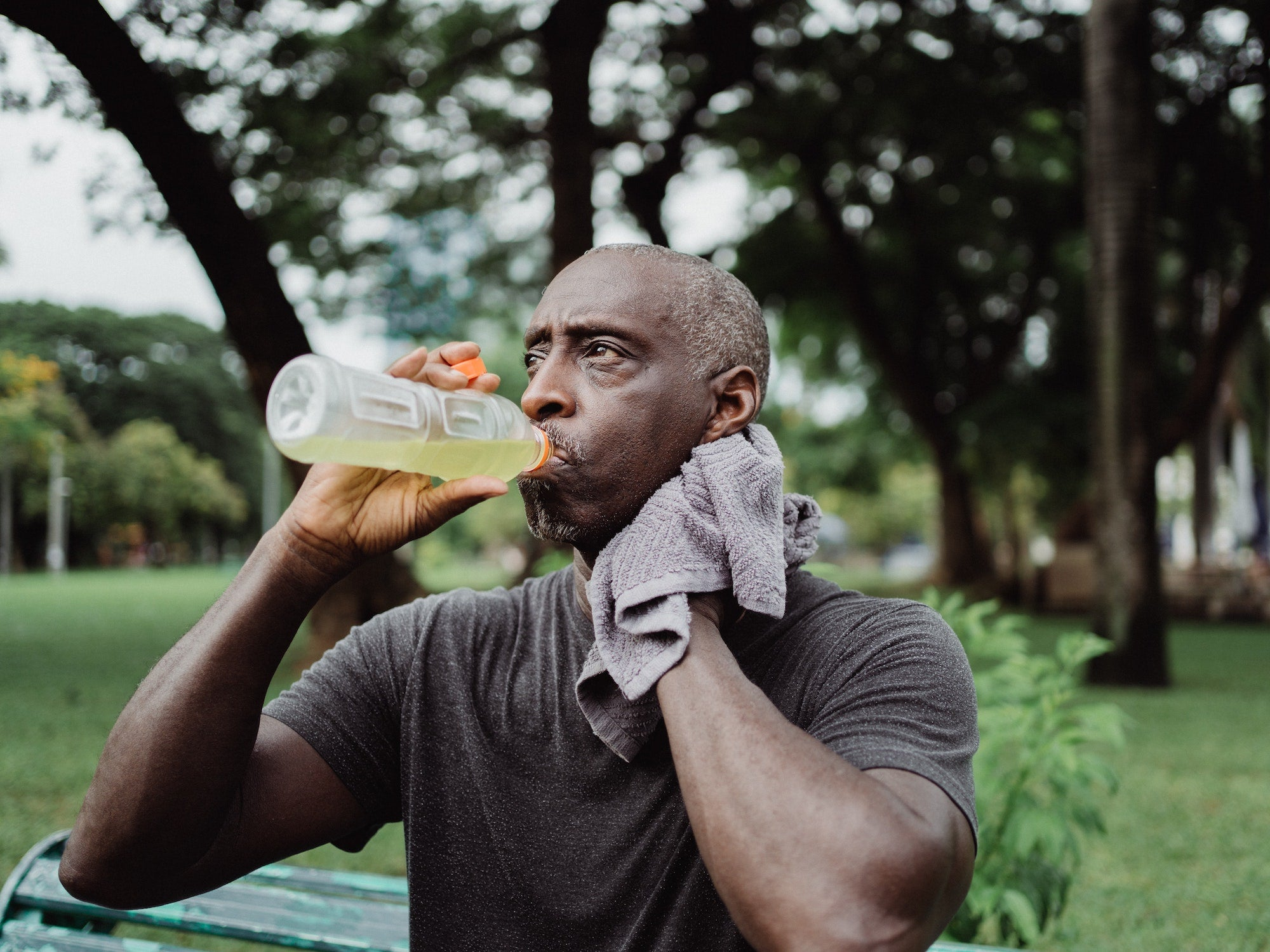 man drinking sports drink sweating sitting on bench