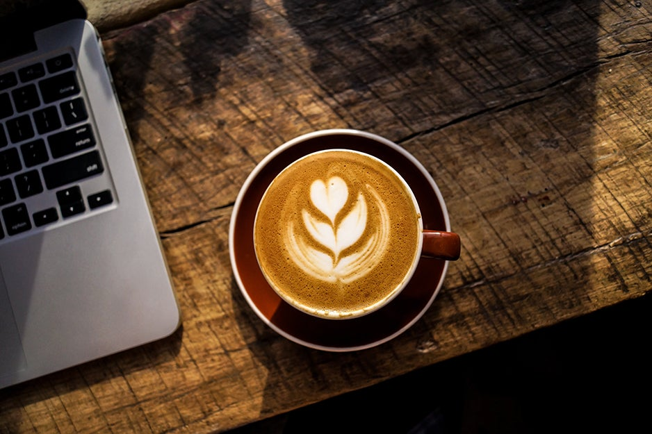 latte on a table next to a laptop