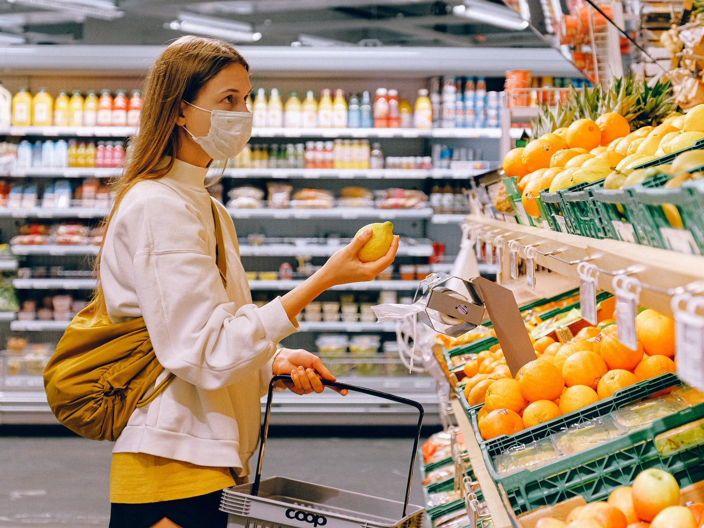 woman wearing a mask in a grocery store holding produce