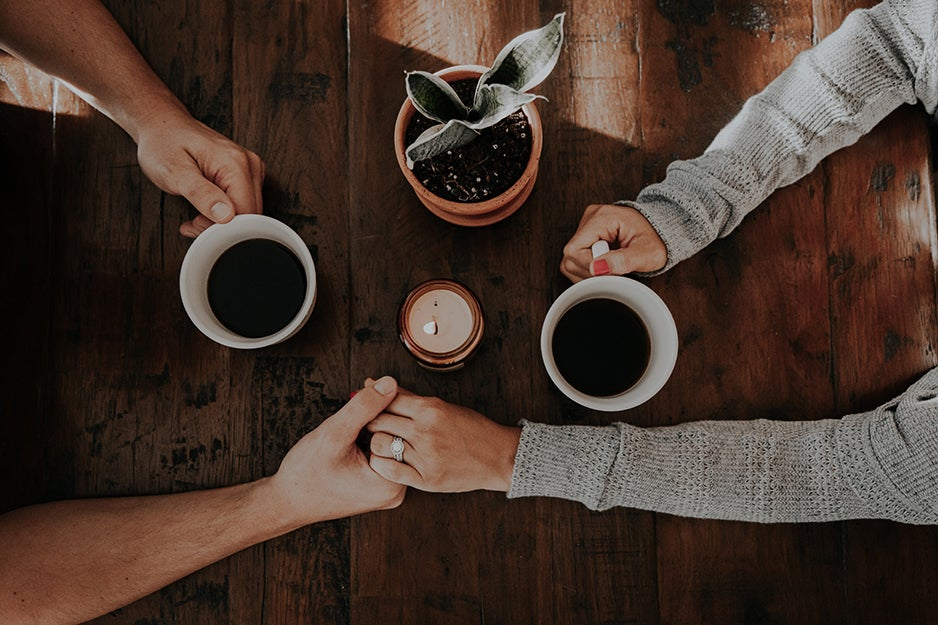 couple drinking coffee holding hands