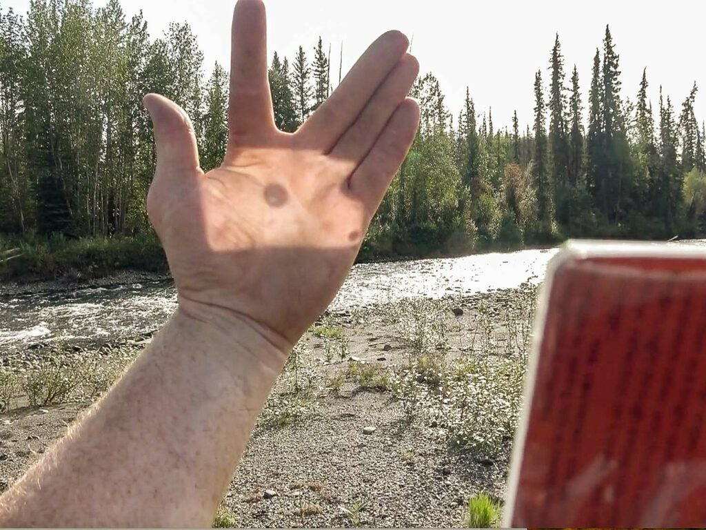 The light reflected onto an outstretched hand to demonstrate a signal mirror's usefulness.