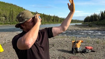 A man holds a survival mirror to his face to reflect on his other hand.