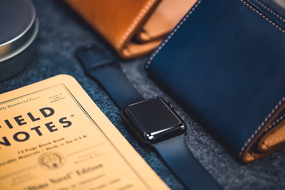 smart watch next to a wallet and notebook