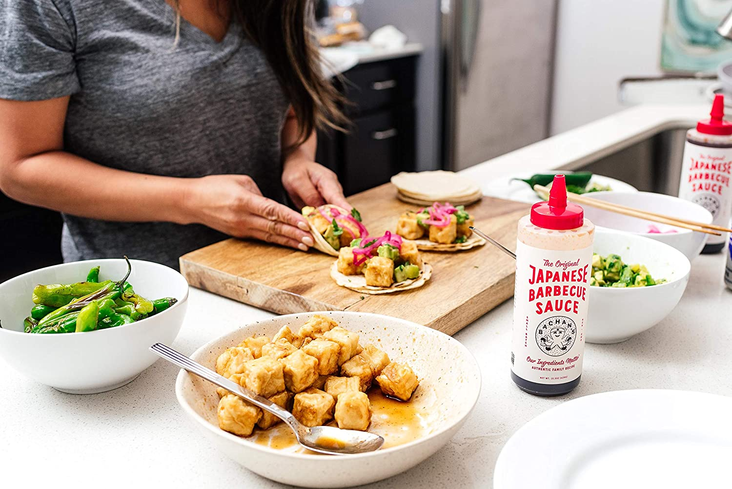 person making tacos with sauce
