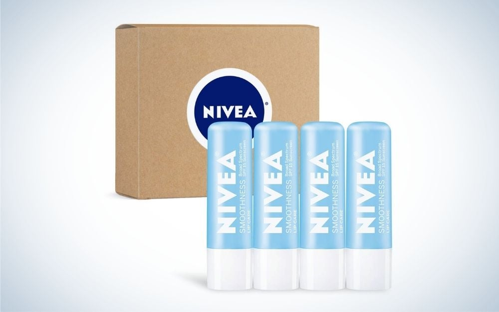 Four Nivea Lip Balm in line with each other in light blue color and a brown wooden box under them.