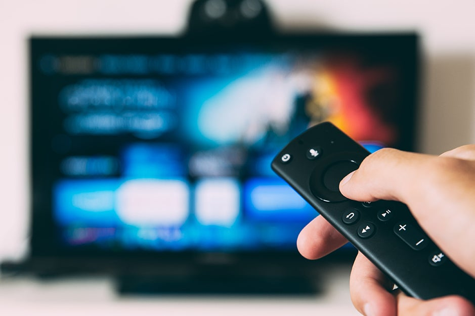 person holding a remote in front of a TV