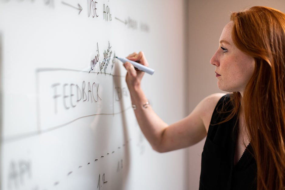 person writing on a white board