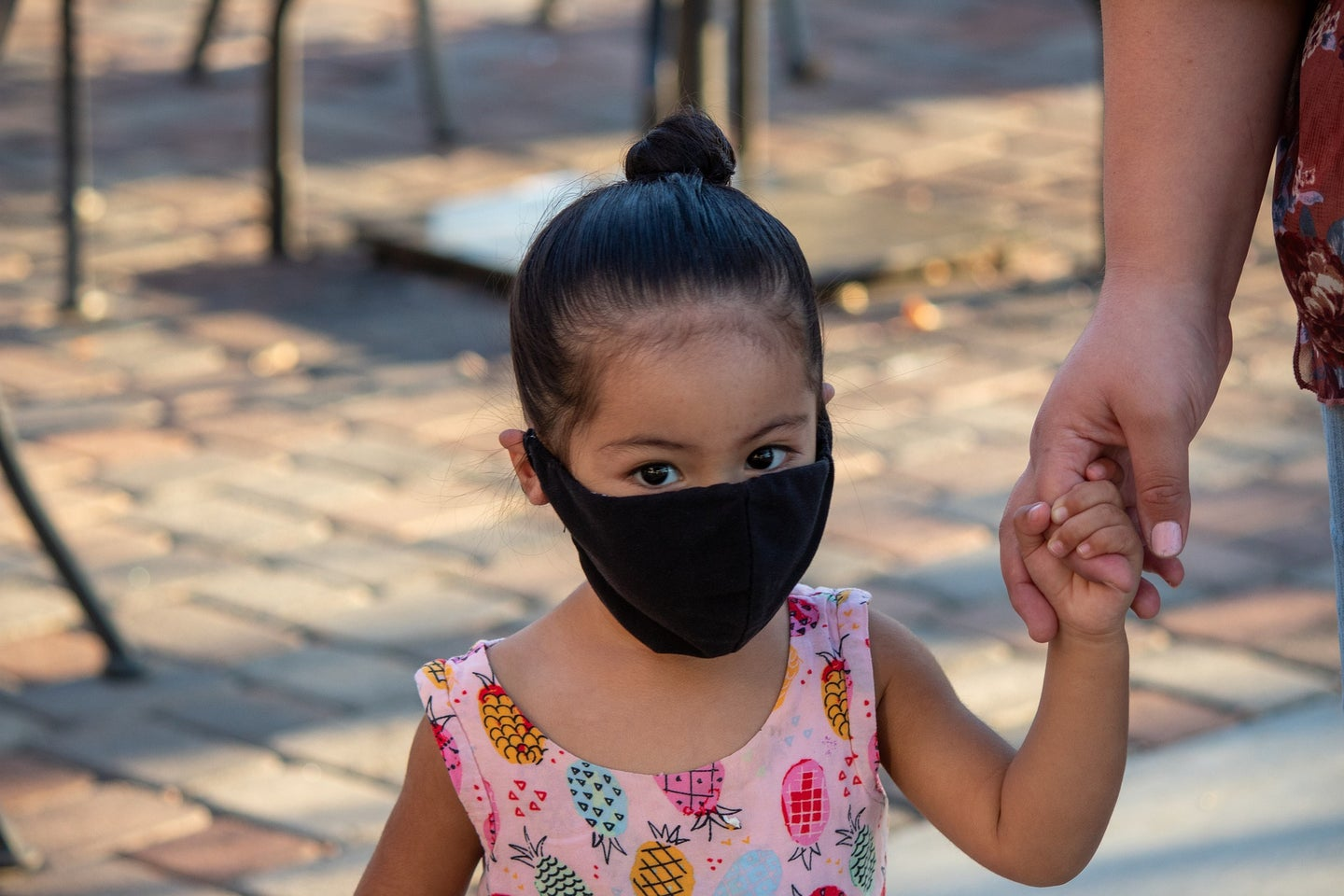 A toddler with a black mask on