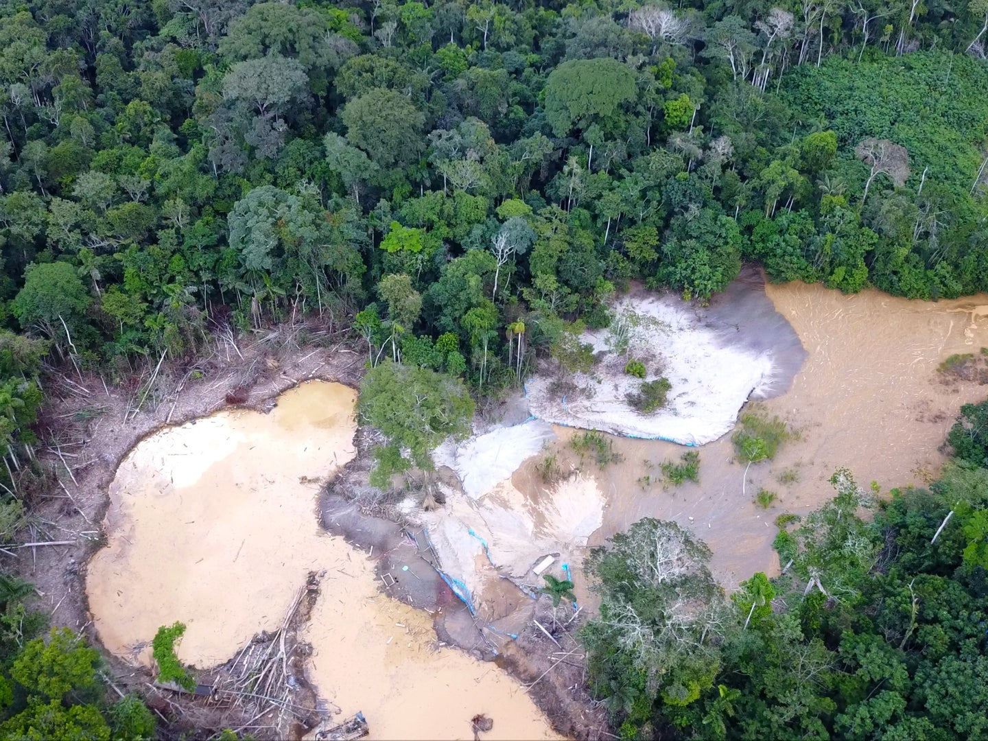 A drone-photograph shows an illegal mine in the middle of the Amazon rainforest. The image shows two artisanal pools, where the miners separate gold from rocks using mercury.