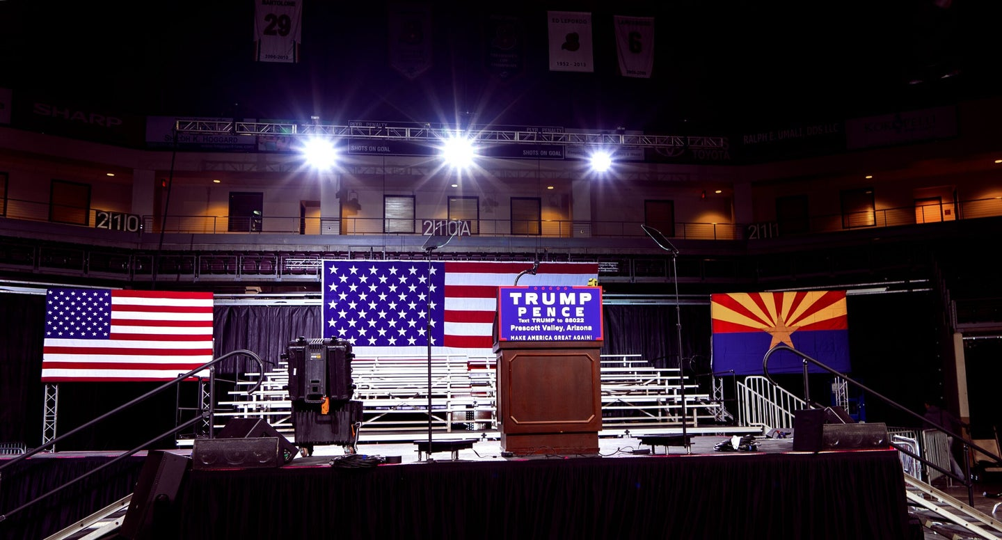 A stage with an American flag and a Trump campaign sign