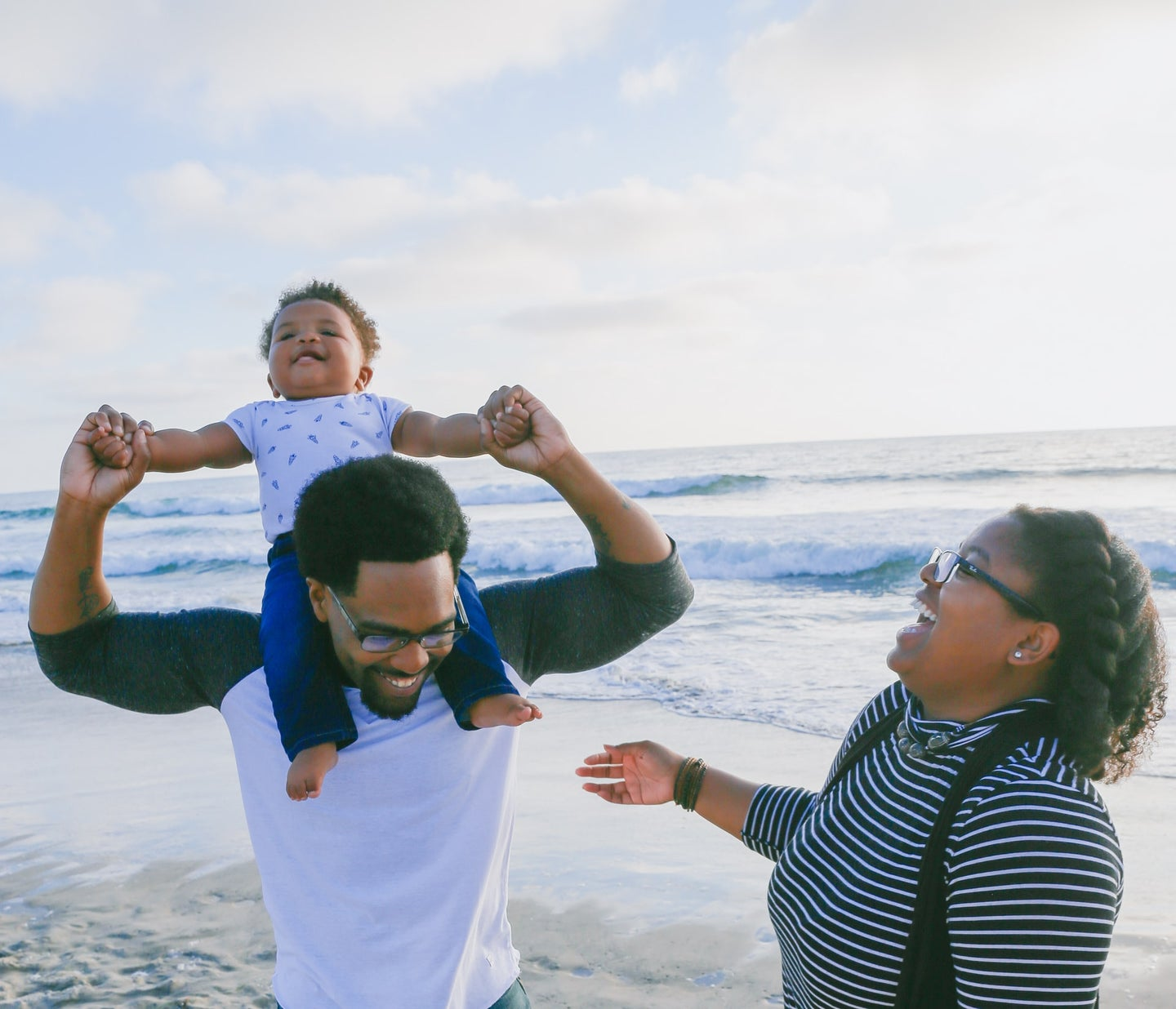 A Black family enjoying the beach with their toddler