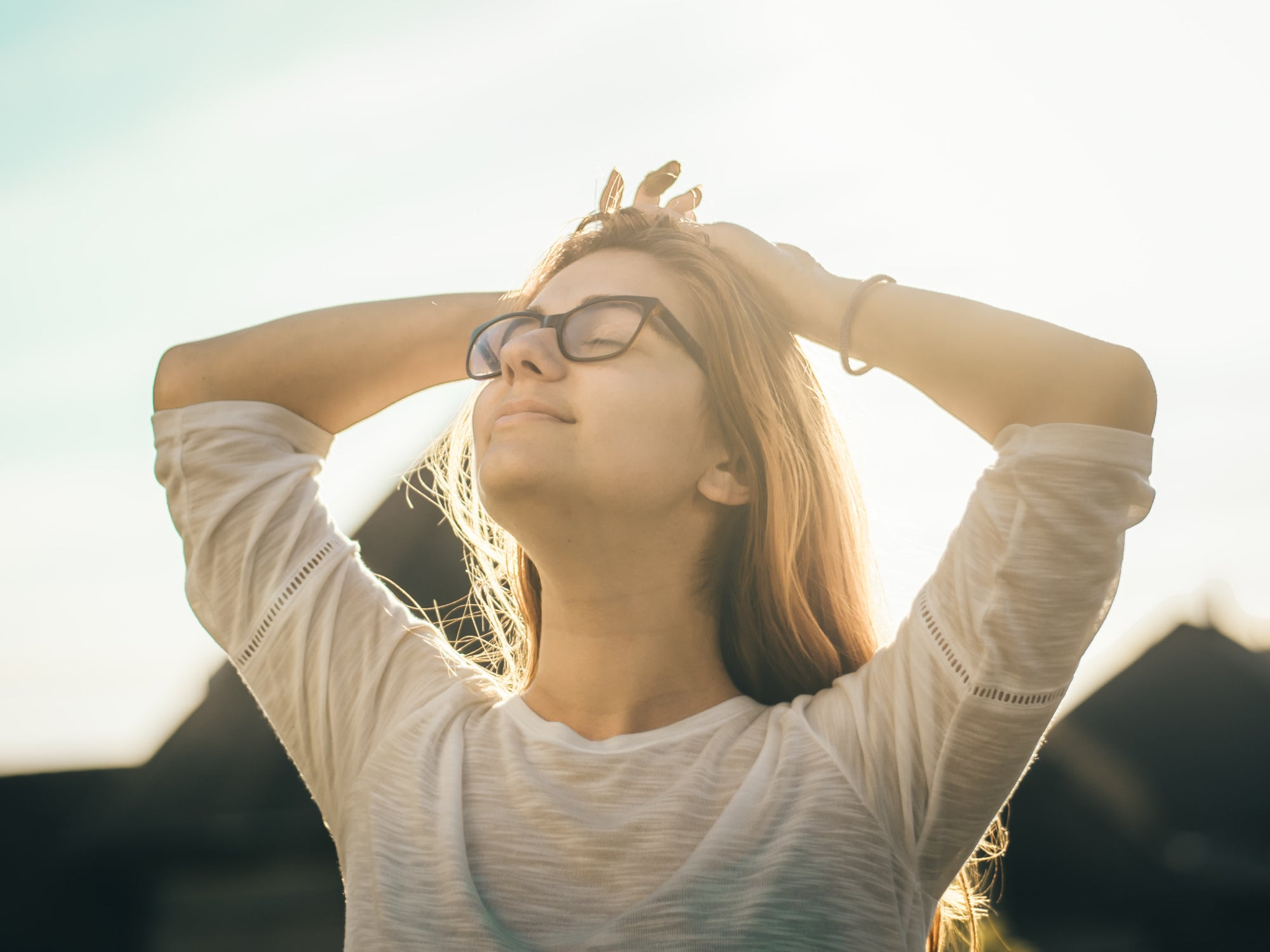 a woman standing calm and happy in the sunlight