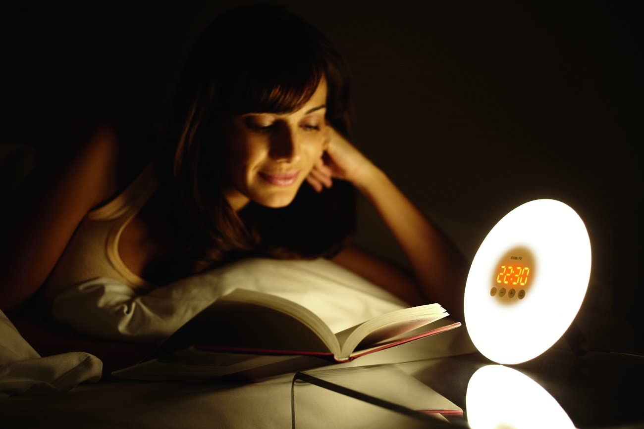 person reading next to a lamp