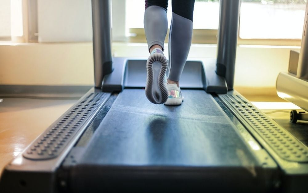 The legs of a girl in tracksuits and white sneakers running on a treadmill all black.