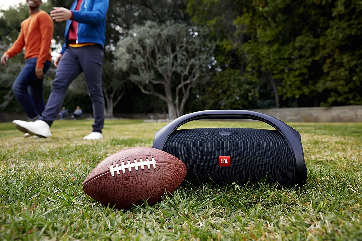 Bluetooth speaker and football in the grass