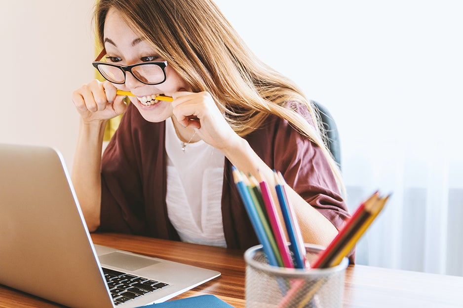 person chewing on a pencil in front of a laptop