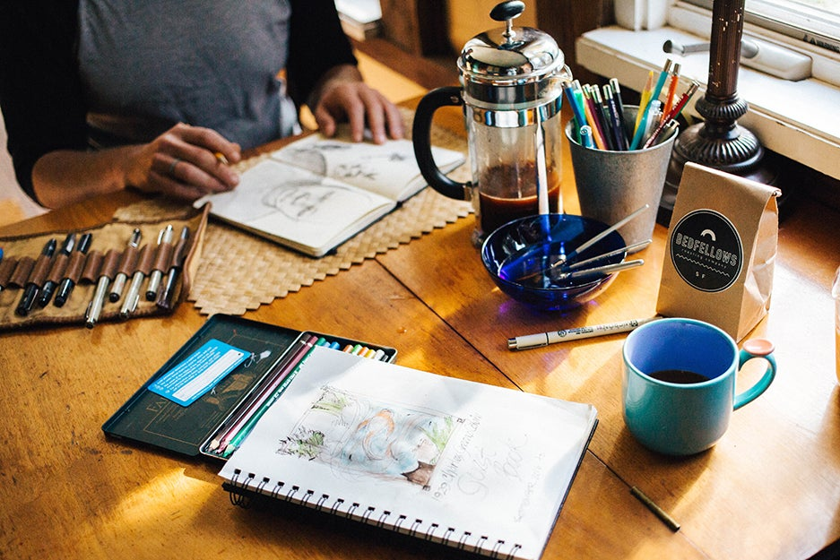 person at table with art supplies and coffee