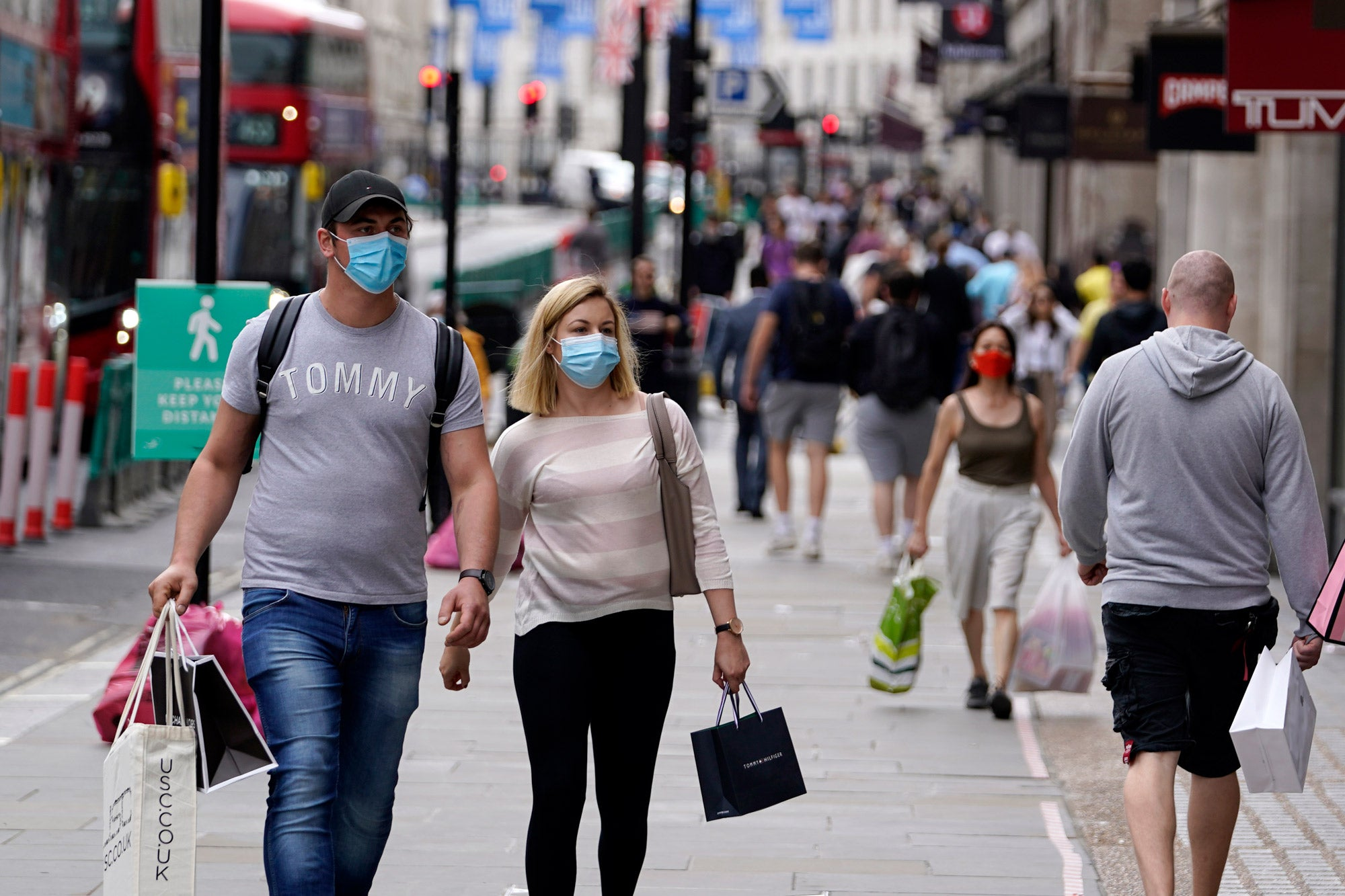 Couple walking while wearing masks