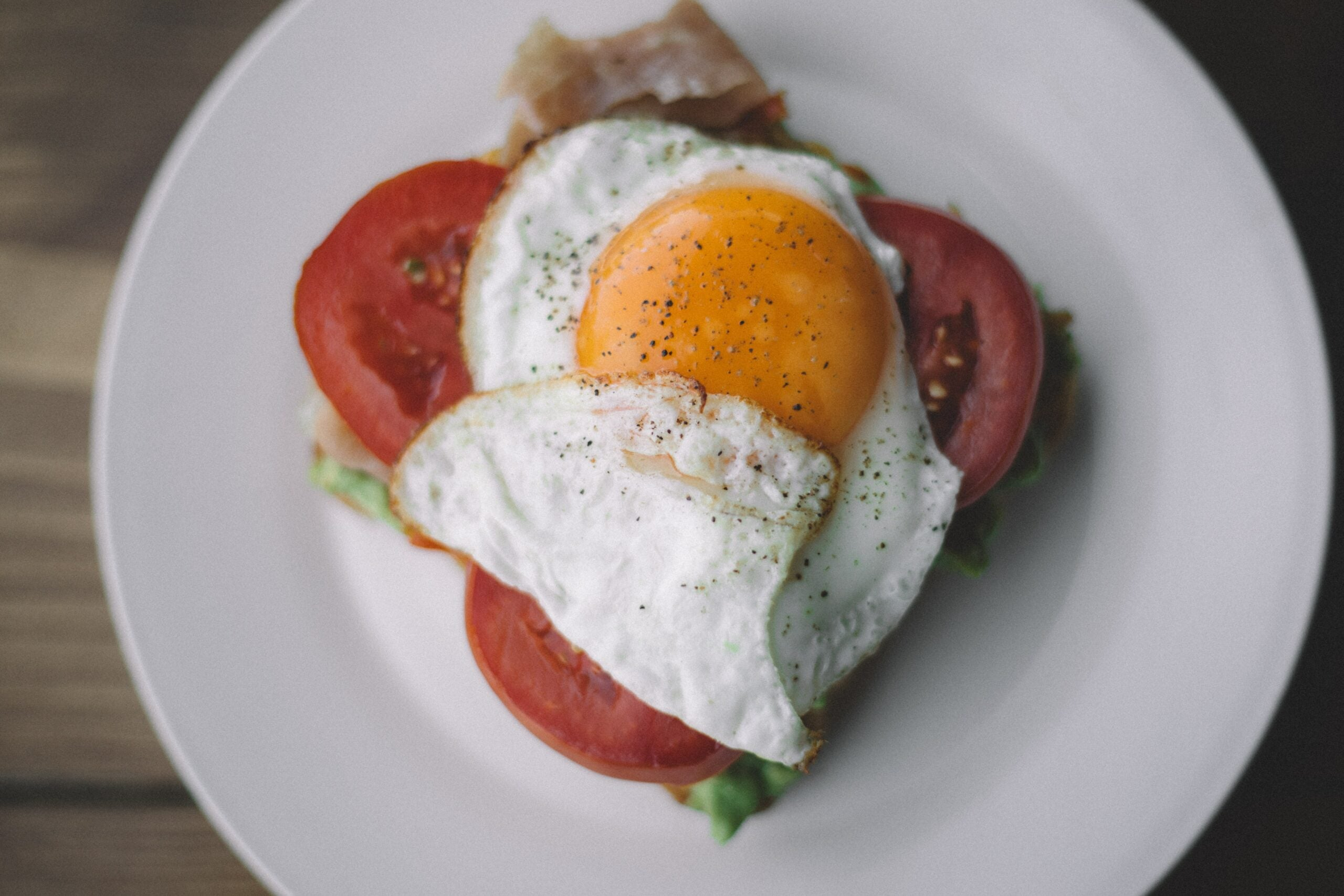 a fried egg on top of tomatoes on a white plate