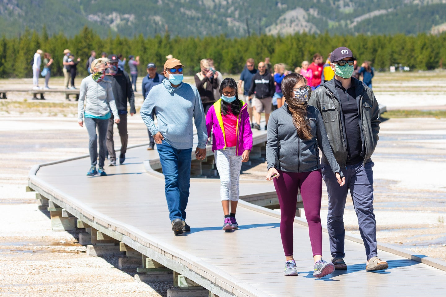 people walking on path at geysers in yellowstone