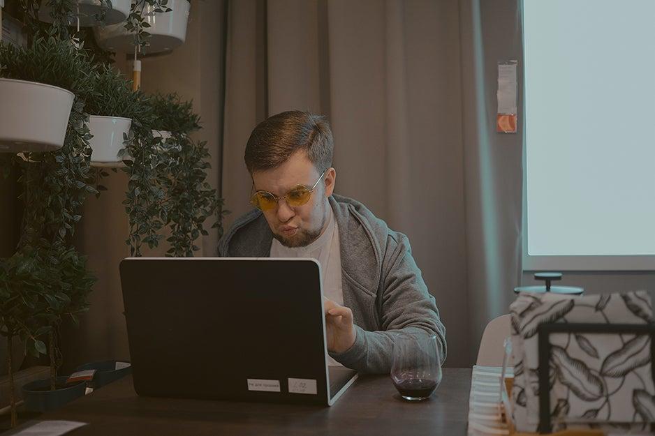 man sitting behind a laptop