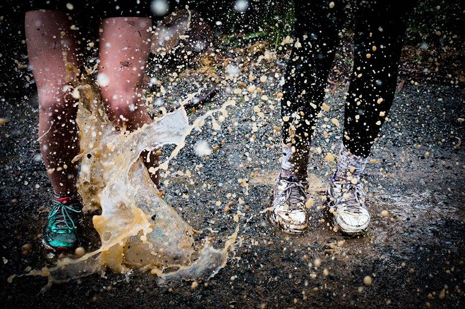 people's feet splashing in muddy water