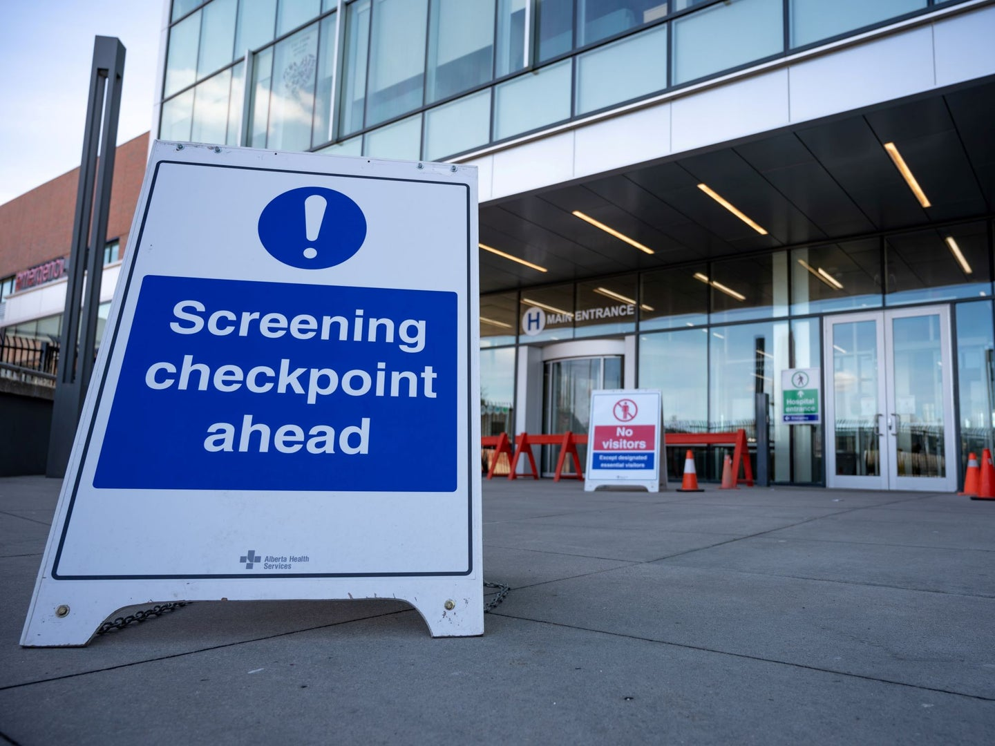 """A sign that says """"Screening checkpoint ahead"""" placed in front of the door to a hospital"""