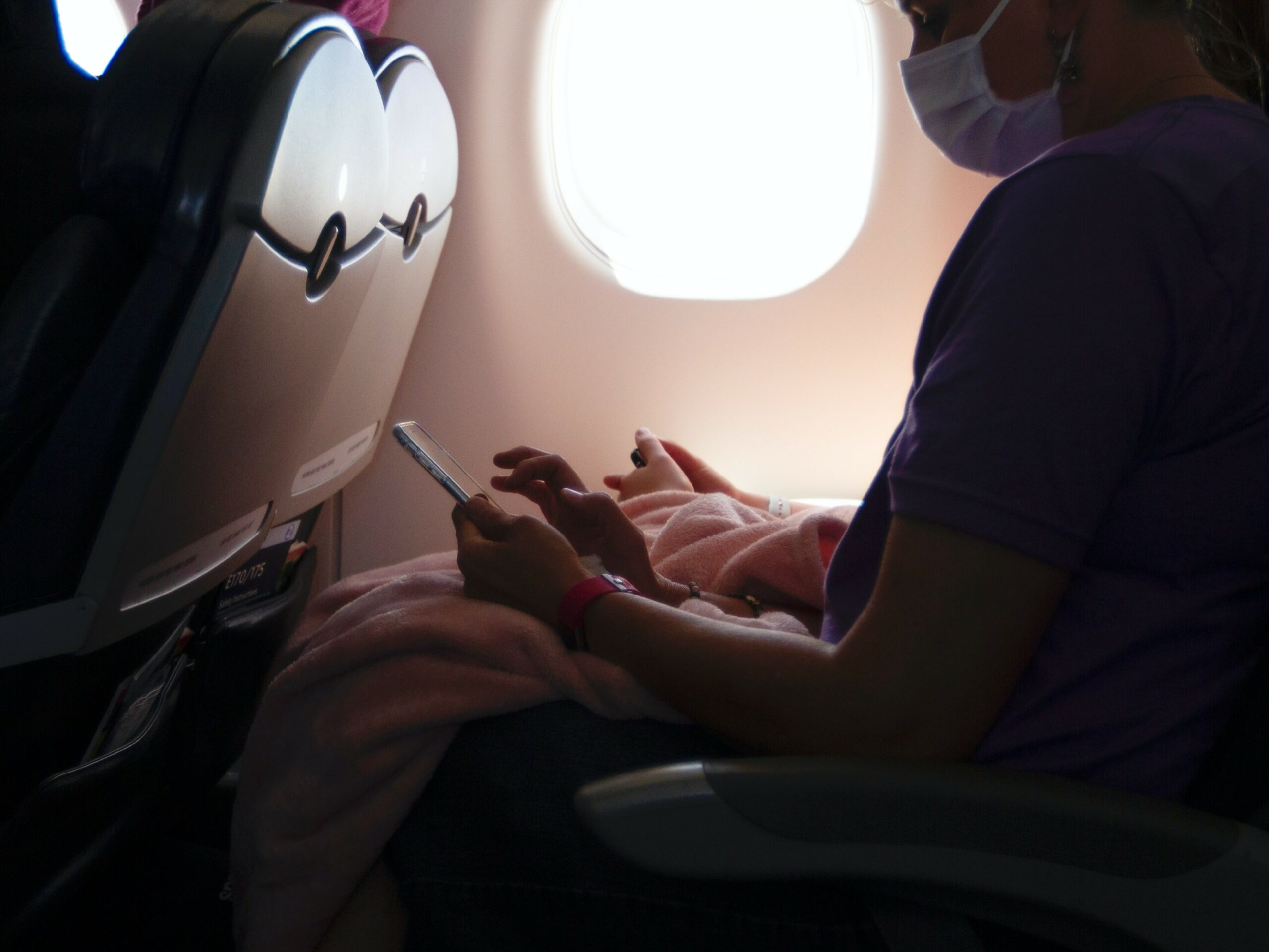 someone in an airplane seat with a mask on