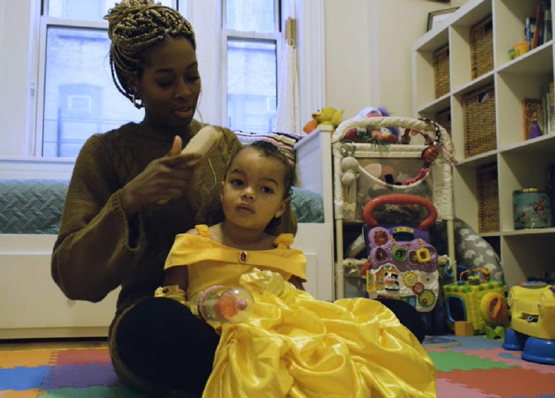 Bianca Jones Marlin brushing her daughter's hair in a playroom