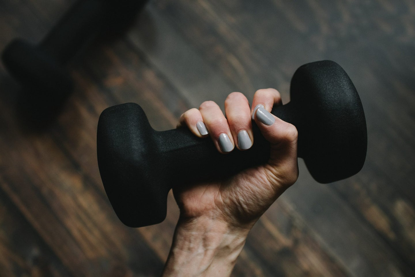 A manicured hand holding a dumbbell