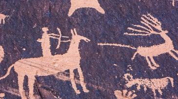 A petroglyph cave painting of a hunter firing an arrow at a deer.