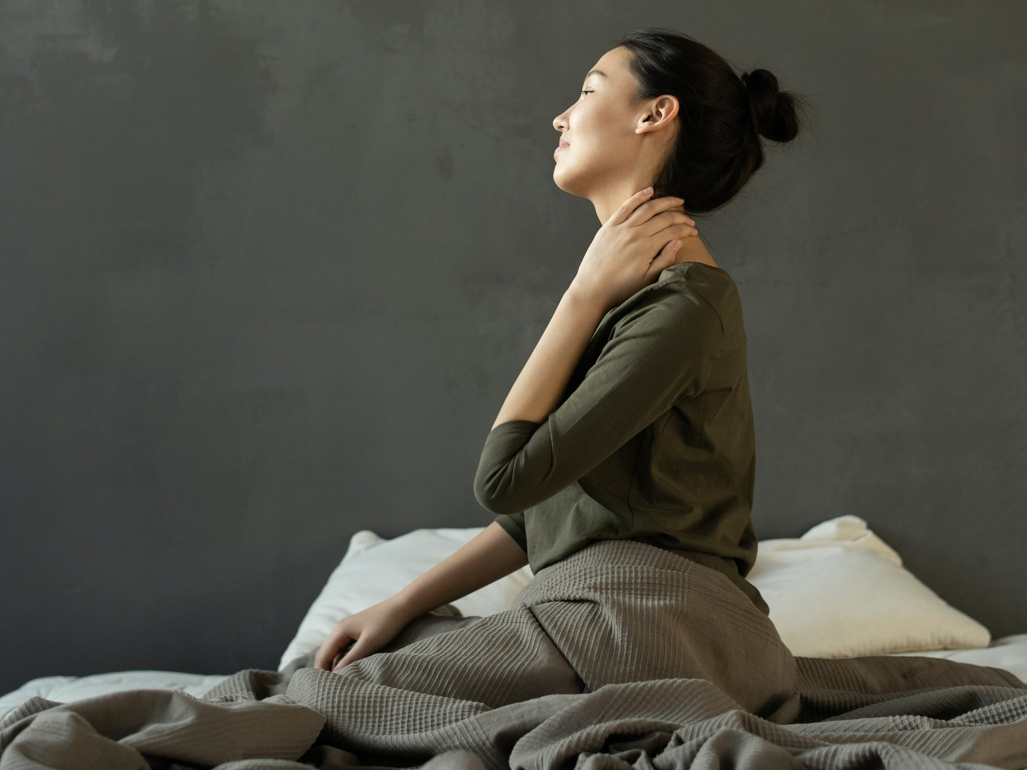 a woman sitting in bed with neck pain