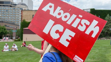 A protester holding an Abolish ICE sign