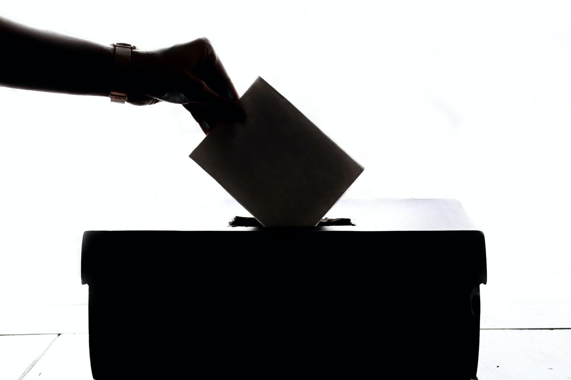 a hand putting a ballot into a box